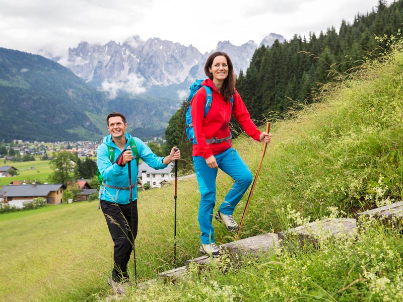 Ein Paar wandert in der Ferienreigon Dachstein Salzkammergut, genau in Gosau mit dem Gosaukamm im Hintergrund.